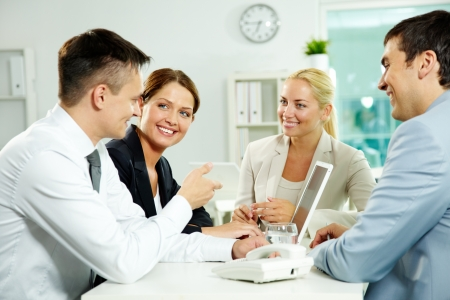 Four business partners sitting in office and interacting at meeting Stock Photo