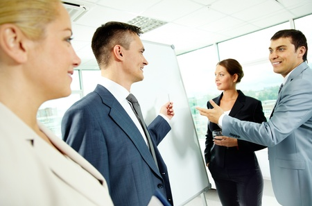staff training: A business man and his partners discussing something on a whiteboard Stock Photo