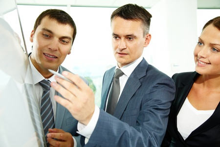 A business man explaining something on a whiteboard to his partners Stock Photo - 10068676