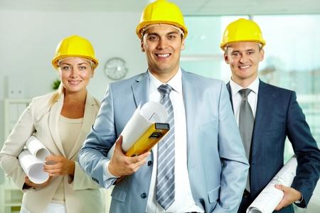 Ein lächelnder Architekt in Helm mit zwei Kollegen in der Nähe von Standard-Bild
