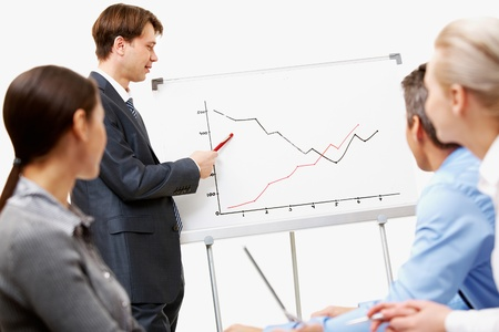 Image of confident man making presentation and pointing at graph on whiteboard photo