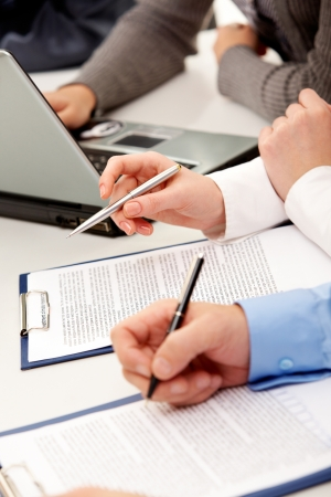 Hands of companions with pens over papers at meeting Stock Photo - 10068739