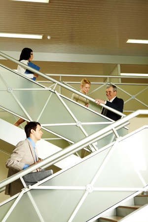Photo of busy partners communicating while going upstairs in office building Stock Photo - 10068698
