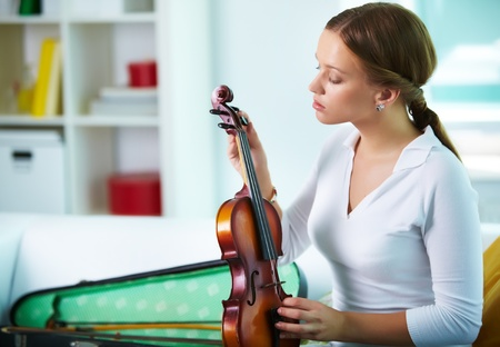 Portrait of a young female tuning the violin photo