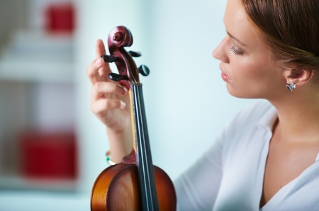 Portrait of a young female tuning the violin Stock Photo - 10068858