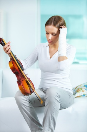 Portrait of a young female with broken arm holding the violin Stock Photo - 10068842