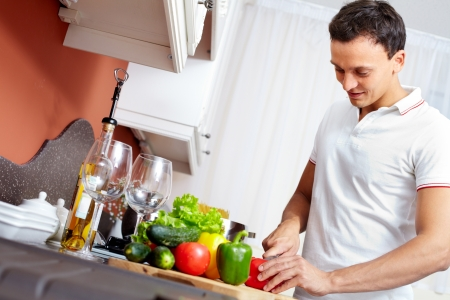low calories: Portrait of young man cutting vegetables in the kitchen  Stock Photo