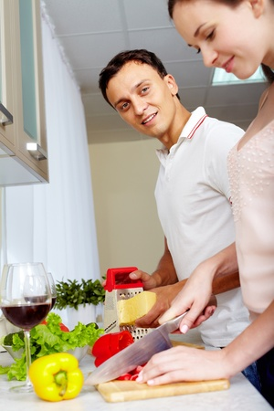 woman knife: Portrait of amorous couple cooking salad in the kitchen