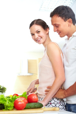 vegetables young couple: Portrait of pretty female cooking salad with her husband near by