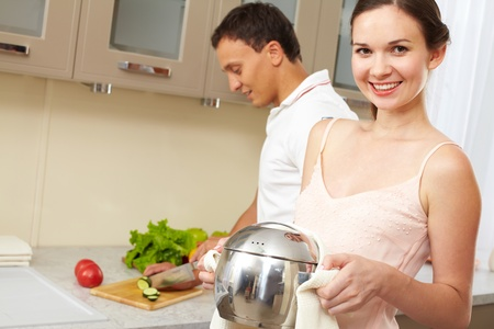 lifestyle looking lovely: Portrait of happy female with pan looking at camera while her husband cooking salad on background  Stock Photo