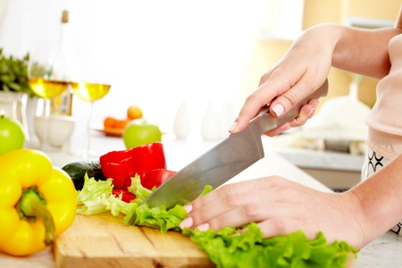 kitchen knife: Close-up of young female cutting lettuce in the kitchen