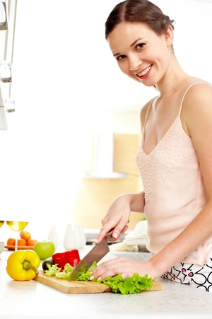 Portrait of happy female cooking vegetable salad Stock Photo - 10068790