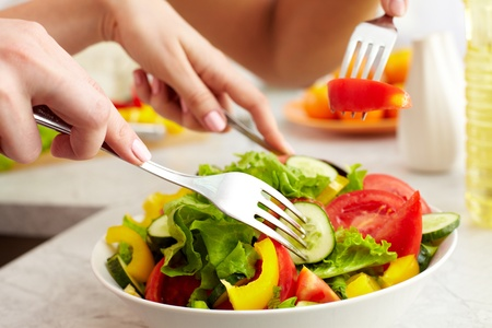 vegetarian food: Close-up of human hands with forks tasting salad  Stock Photo