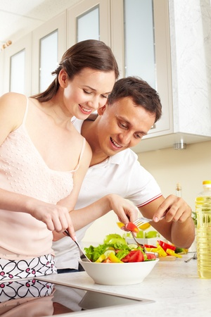 Portrait of happy couple with forks tasting salad  photo