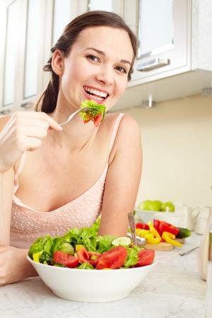 meisje eten: Portret van een meisje eet salade en kijken naar de camera