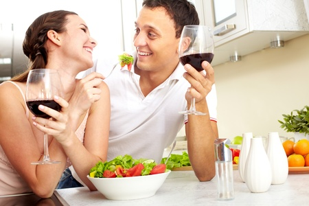 Image of happy couple with glasses of red wine eating salad  photo