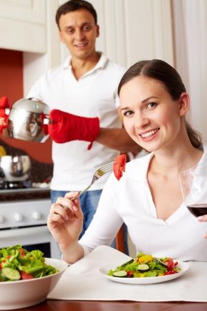 meisje eten: Portret van een meisje het eten van salade en kijken naar de camera Stockfoto