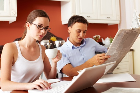 newspaper reading: Portrait of handsome man eating snacks with milk in the kitchen while typing  Stock Photo