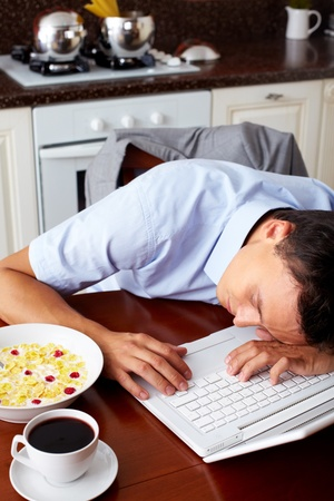 Portrait of man sleeping on laptop keypad with bowl of snacks and cup of coffee near by in the kitchen photo