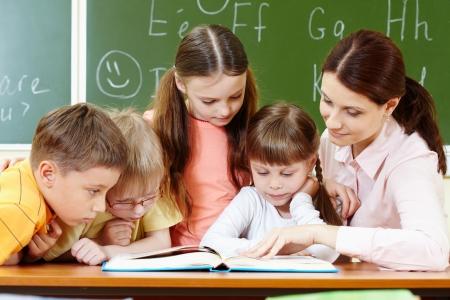 classroom teacher: Portrait of smart schoolchildren and their teacher reading book in classroom