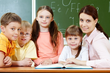 Portrait of smart schoolchildren and their teacher looking at camera in classroom photo