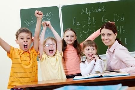schoolchild: Portrait of joyful schoolchildren showing gladness with their teacher near by