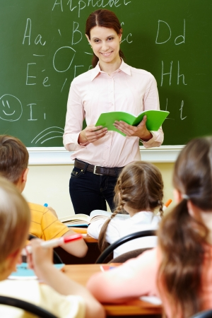 Portrait of smart teacher with exercise book looking at schoolkids in classroom Stock Photo - 10122226