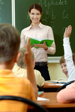 female teacher: Portrait of smart teacher with exercise book looking at schoolkids in classroom