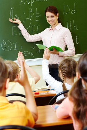 teacher: Portrait of smart teacher pointing at blackboard and looking at schoolkids in classroom