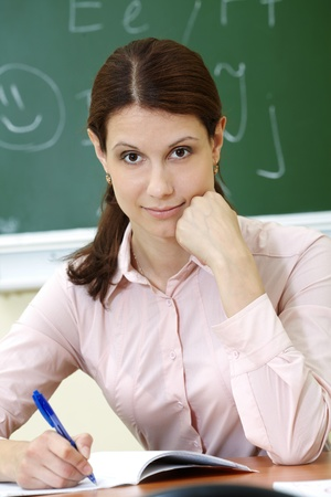 adult classroom: Portrait of smart teacher at workplace looking at camera Stock Photo