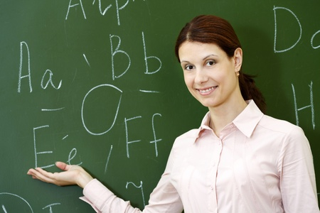 Portrait of smart teacher pointing at letters on blackboard and looking at camera photo