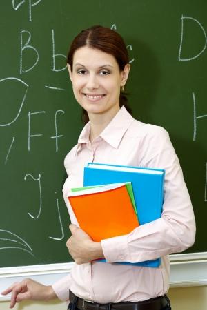 leraar: Portret van slimme leraar met boeken door het bord camera kijken