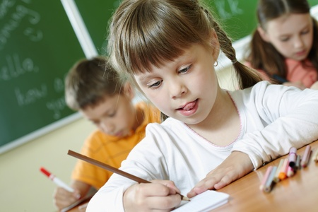 Portrait of smart schoolgirl drawing at lesson in classroom photo