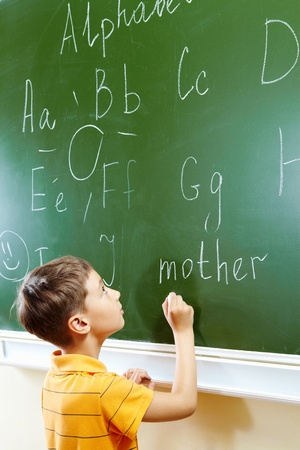 primary education: Portrait of smart schoolchild by the blackboard looking at it