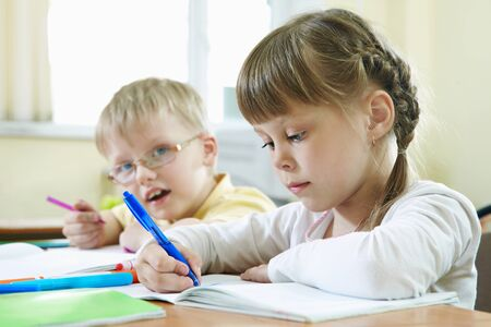 Portrait of smart schoolkids drawing at lesson in classroom photo
