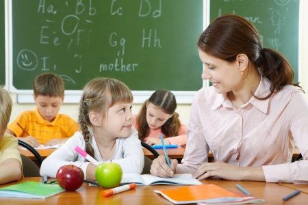 classroom teacher: Portrait of smart girl and her teacher looking at each other at lesson in classroom