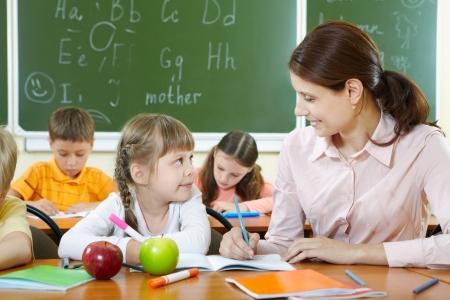 educadores: Retrato de una chica inteligente y su profesor mirando en otra lecci�n en aula