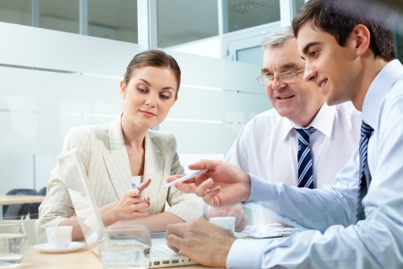A business team of three sitting in office and planning work Stock Photo - 10122230