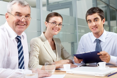 Smiling business partners looking at camera in office photo