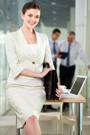 Smiling businesswoman with briefcase looking at camera in working environment photo