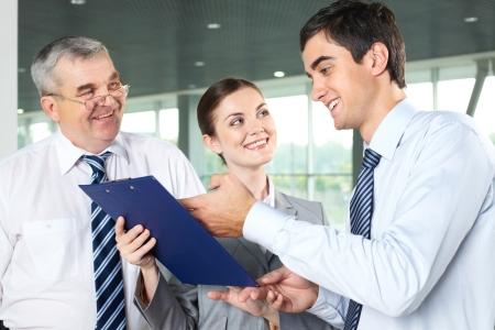 communication occupation: Sorridente uomo spiegando documento aziendale, mentre i suoi partner guardando lui