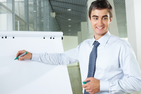 Smiling businessman presenting new project to partners on a whiteboard photo