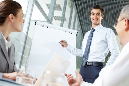 Smiling business man presenting new project to his partners on a whiteboard Stock Photo - 10122223
