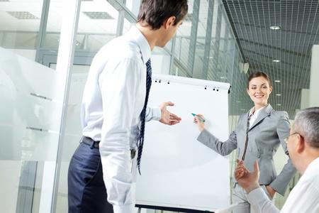 財源: 会議でホワイト ボード上のアイデアを説明する若い女性のイメージ