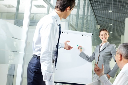 Image of young woman explaining ideas on whiteboard at meeting photo