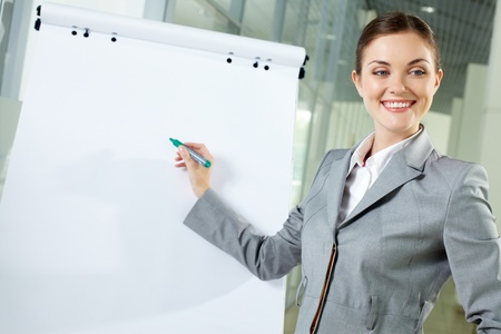 Image of young woman pointing at whiteboard at meeting photo
