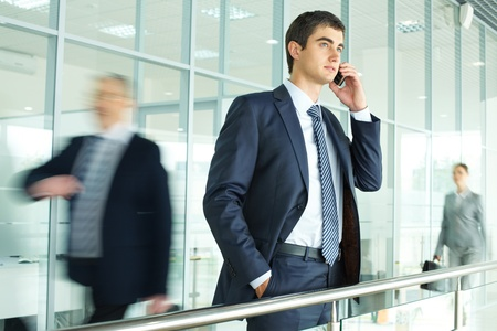 Businessman standing by banisters and calling with walking people on background Stock Photo - 10122227