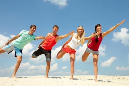 Cuatro amigos felices haciendo ejercicio en la playa