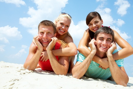 Two happy couples lying on sand and looking at camera Stock Photo - 10130644