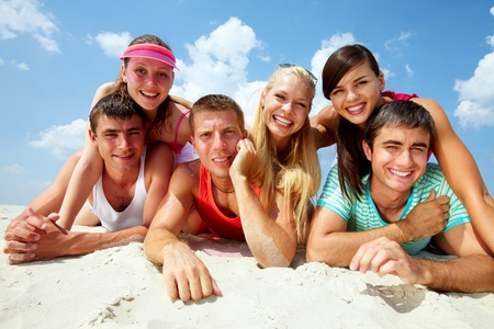 humeur: Trois heureux couple couch� sur le sable et regardant la cam�ra